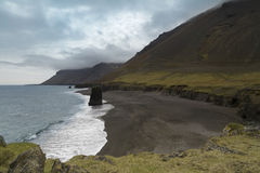 Icelandic shoreline panorama. Horizontal view of an Icelandic beach with a huge rock formation in the middle Stock Photography