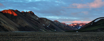 Icelandic valley. Beautiful and colorful icelandic valley during the sunset, famous part called Landmanallaugar, with mountains tops illuminated with lots of Royalty Free Stock Photography