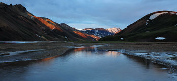 Icelandic valley. Beautiful and colorful icelandic valley during the sunset, famous part called Landmanallaugar with water in foreground and mountains tops Royalty Free Stock Photo