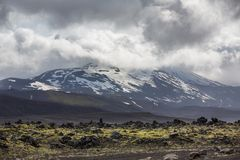 Icelandic volcano with snow and cloudy sky Stock Images