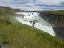 Icelandic waterfall with green surrounding fields Royalty Free Stock Photography