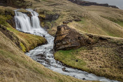 Icelandic waterfall and stream. Icelandic landscape with waterfall and rushing stream flowing through rolling grassy moorland Stock Photography