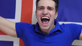 Icelandic Young Man Celebrates holding the Flag of Iceland in Slow Motion. High quality royalty free stock photography