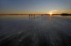Iceskating on a dutch lake. During sunset Stock Photo