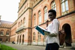 Ich bestehe diese Prüfung Glückliche Weile des jungen afroen-amerikanisch Studentenblickes las Anmerkungen von den Lehrbüchern, e lizenzfreie stockbilder