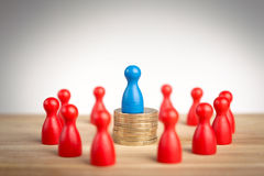 Ich business leader concept with blue figure on top of coin stac Stock Photo