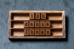 Ich danke Ihnen. Thank you in German translation. Vintage box, wooden cubes thankful phrase message written with old. Style letters. Gray stone textured Stock Image