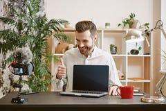 Ich empfehle es! Netter bärtiger Technologie Blogger, der auf neuen Laptop, Daumen und das Lächeln zeigend zeigt stockfoto
