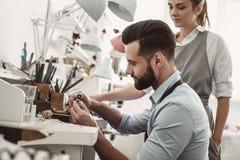 Ich helfe Ihnen Nahaufnahmeporträt des jungen männlichen Assistenten, der einen Ring während weiblicher Juwelier poliert, den Pro lizenzfreie stockfotos