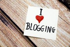 Ich liebe blogging Mitteilung mit rotem Herzsymbol auf dem Weißbuch mit Retro- hölzernem Hintergrund On-line-Bloggers-Begriffsmit Stockfoto