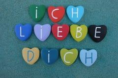 Ich Liebe Dich на пестротканых каменных сердцах над влажным песком Стоковое Фото