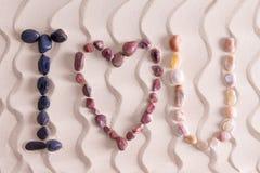 Ich liebe dich in den bunten Steinen auf goldenem Strandsand Stockbilder