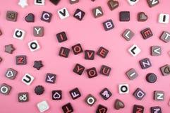 Ich liebe dich graviert in der Schokolade auf farbigem Hintergrund stockbilder