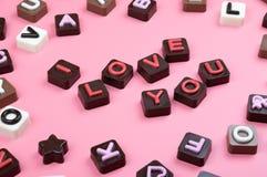 Ich liebe dich graviert in der Schokolade auf farbigem Hintergrund stockfotos