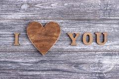 Ich liebe dich hölzerne Beschriftung, grauer Hintergrund, Postkarte glücklicher Valentinstag, flache Lage lizenzfreies stockfoto