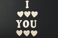 Ich liebe dich mit Buchstaben und hölzernen Herzen auf schwarzem Hintergrund Lizenzfreie Stockbilder