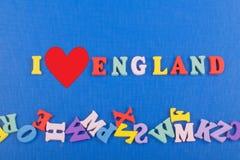 Ich liebe ENGLAND-Wort auf dem blauen Hintergrund, der von den hölzernen Buchstaben des bunten ABC-Alphabetblockes verfasst wird, Stockbilder
