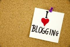 Ich liebe mein Blogging geschrieben auf das weiße Schild, das zu einer KorkenAnschlagtafel festgesteckt wird Stockbilder