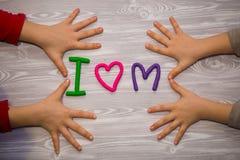 Ich liebe Muttertext vom Plasticine mit den Kinderhänden auf weißem hölzernem Hintergrund Glücklicher Muttertag Spaßkinderhandgem stockbilder