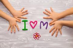 Ich liebe Muttertext vom Plasticine mit den Kinderhänden auf weißem hölzernem Hintergrund Glücklicher Muttertag Spaßkinderhandgem stockfotos