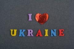 Ich liebe UKRAINE-Wort auf dem schwarzen Bretthintergrund, der von den hölzernen Buchstaben des bunten ABC-Alphabetblockes verfas Stockfotos