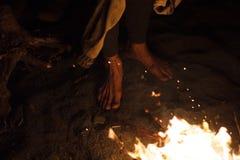 Ich wärme meine Füße durch die Nachtfeuerstellung auf dem Sand stockfoto