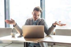 Ich weiß nicht! Porträt des verwirrten hübschen bärtigen jungen Freiberuflers im grauen Blazer sitzen im Café und machen Videoanr lizenzfreies stockfoto
