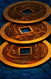 IChing. Three gold coins used for i-ching prophecy in gold lightning Royalty Free Stock Image