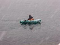 Ichthyologisten på det uppblåsbara fartyget återställer förtjänar från havet i tungt snöfall arkivfoton