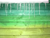 Icicles in front of a turquoise yellow green wooden wall as a christmas background royalty free stock photography