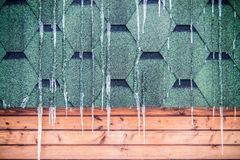 Icicle hanging on a roof of wooden house. Icicle hanging on a roof, cold winter stock image