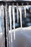 Icicle. A macro of a row of icicles with a sky background Stock Photo
