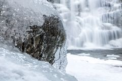 The water stream is froze on the stone. Icicle on a rock in a forest, close-up view, waterfall on background. The water stream is froze on the stone in the woods royalty free stock photo