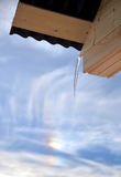 Icicle on roof of house on background of rainbow Royalty Free Stock Photo