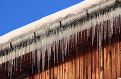 Icicles. On wooden house in winter time stock photos