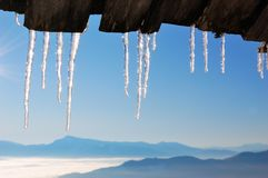 Icicles. The icicles which are hanging down from a wooden roof, against the blue sky and mountains Stock Photos