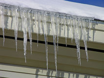 Icicles. Hanging off a roof stock photo