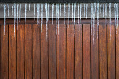 Icicles above a wooden facade Stock Image