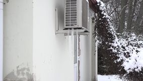 Icicles on the air conditioner hanging on house wall in winter time. 4K. Icicles on the air conditioner hanging on house wall in winter time. Zoom out shot. 4K stock video
