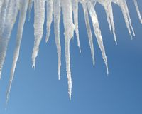 Icicles on a blue sky. White icicles drop from a blue sky Stock Image