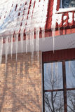 Icicles on building roof at winter day Royalty Free Stock Photo