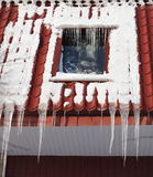 Icicles on building roof at winter day Stock Photos