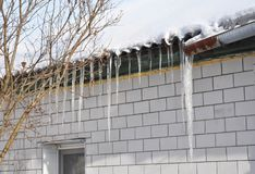 Icicles damage roof and gutter. Ice Damming. Close up on Icicles damage roof and gutter. Ice Damming Stock Images