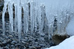 Icicles dangling above pebbled beach Royalty Free Stock Photos