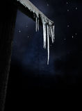 Icicles on dark winter sky Royalty Free Stock Images