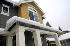 Icicles on house roofline. Northwest winter dresses up the house with a necklace of icicles Stock Photos