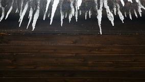 Icicles drip from a wooden stock footage