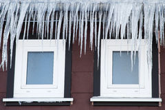 Icicles in front of two windows Royalty Free Stock Photos