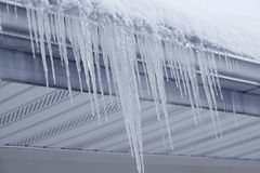 Icicles from Gutter. Icicles hanging on gutter eaves of roof in winter time Royalty Free Stock Photo