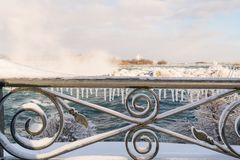 Niagara Falls in Winter with snow and ice. Icicles on handrail at Niagara Falls, Canada, falls in background stock images